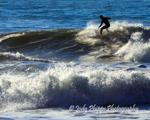 A surfer catching a wave at Indian Beach in Ecola State Park.