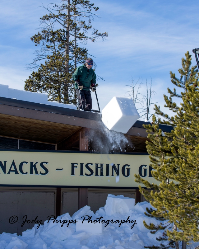 John Henry clearing snow from the roofs of the buildings at Canyon Village in Yellowstone National Park