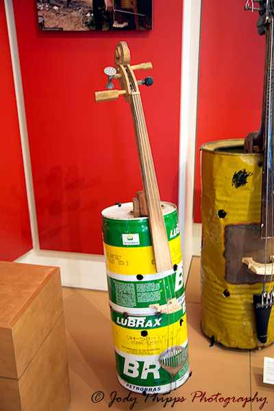 "A Cello made of a metal automotive container, spatula, used strings, recycled wood and tuning pegs and made by Nicolas ""Cola"" Gomez."